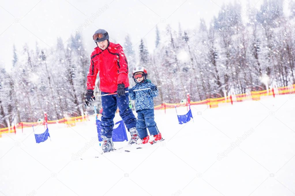 Happy little boy learning skiing with his father in Swiss Alps