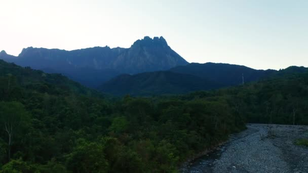 Aerial drone footage of beautiful rural Village with green forest and clean river with Majestic Mount Kinabalu View.
