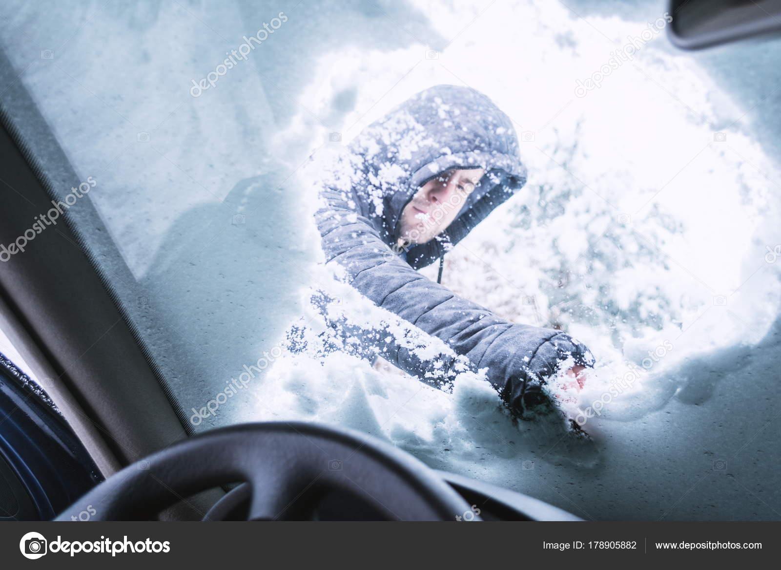 Homme Nettoyage De La Neige Sur Son Verre De Fenêtres De Voiture