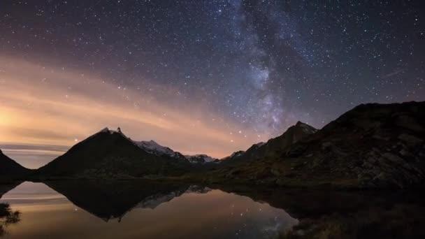Zdánlivé otáčení Mléčné dráhy a hvězdnou oblohu nad zasněžené horský hřeben, odráží na idylické apine jezero. Souhvězdí Orion přichází zleva na konci. Čas zanikla 4k videa