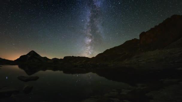 Zdánlivé otáčení Mléčné dráhy a hvězdnou oblohu nad zasněžené horský hřeben, odráží na idylické apine jezero. Čas zanikla 4k videa