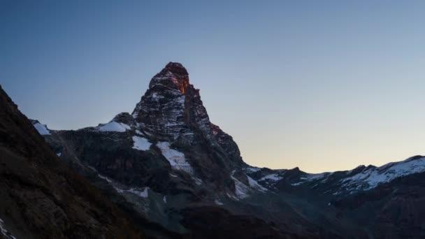 Sunrise light over the elegant Matterhorn or Cervino summit (4478 m), italian side, Valle dAosta. Time lapse 4k video.