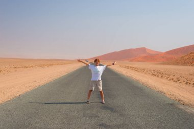 Woman with outstretched arms standing on gravel road crossing the Namib desert, in the Namib Naukluft National Park, main travel destination in Namibia, Africa.