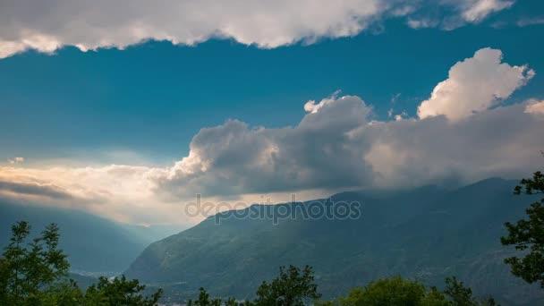 Zasněžené horské hřebeny a vrcholy s pohyblivými mraky nad Alpy v létě, Provincie Torino, Itálie. Časová prodleva při západu slunce. Posuvné verze.