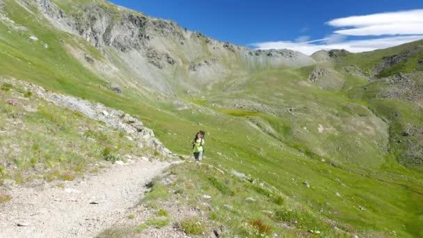 Žena, trekking v idylické horské krajině na chodník přes kvetoucí zelené louce uprostřed skalnatého pohoří vysoké nadmořské výšce a vrcholy. Letní dobrodružství na Italské Alpy
