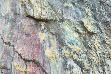 Close up of colorful rock surface, natural background, pattern and texture. Metamorphic white quartzite folded and fractured together with red coarse sandstone, due to the power of geologic crustal mo