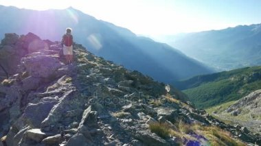 Woman trekking in high altitude rocky mountain landscape. Summer adventures on the Italian French Alps.
