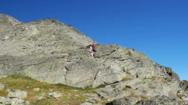 Woman climbing on high altitude rocky mountain cliff. Summer adventures on the Italian French Alps