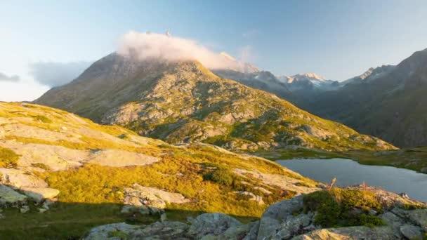 Horské vrcholy a alpské jezero s pohyblivými mraky nad Alpy v létě, Maurienne, Savojsko, Francie. Časová prodleva při západu slunce do soumraku