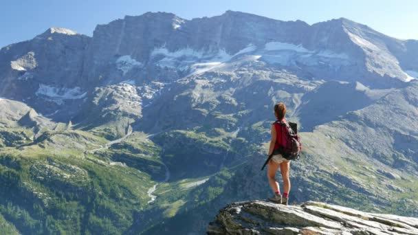 Žena stojící na vrchol hory ve vysoké nadmořské výšce skalnaté krajině s ledovci a peak v pozadí. Letní dobrodružství na Alpy. Zpomalený pohyb
