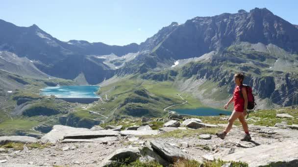 Žena na chodník v idylické horské krajině s modré jezero, vrchol vysoké hory a ledovce. Letní dobrodružství na Alpy