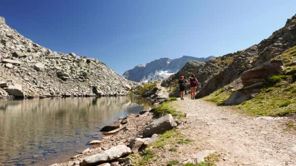 Couple hiking on footpath in idyllic mountain landscape with crystal water lake, high mountain peak and glacier. Summer adventures on the Alps.