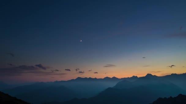 Den noc časová prodleva z vysoko v Alpách. Barevný západ slunce nad vrcholky hor a mlhy v údolích, pohybující se mraky, nastavení měsíc, rotující hvězdy a mléčné dráhy. Posuvné verze