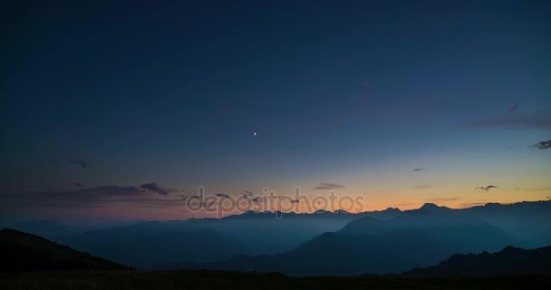Den noc časová prodleva z vysoko v Alpách. Barevný západ slunce nad vrcholky hor a mlhy v údolích, pohybující se mraky, nastavení měsíc, rotující hvězdy a mléčné dráhy. Statická verze