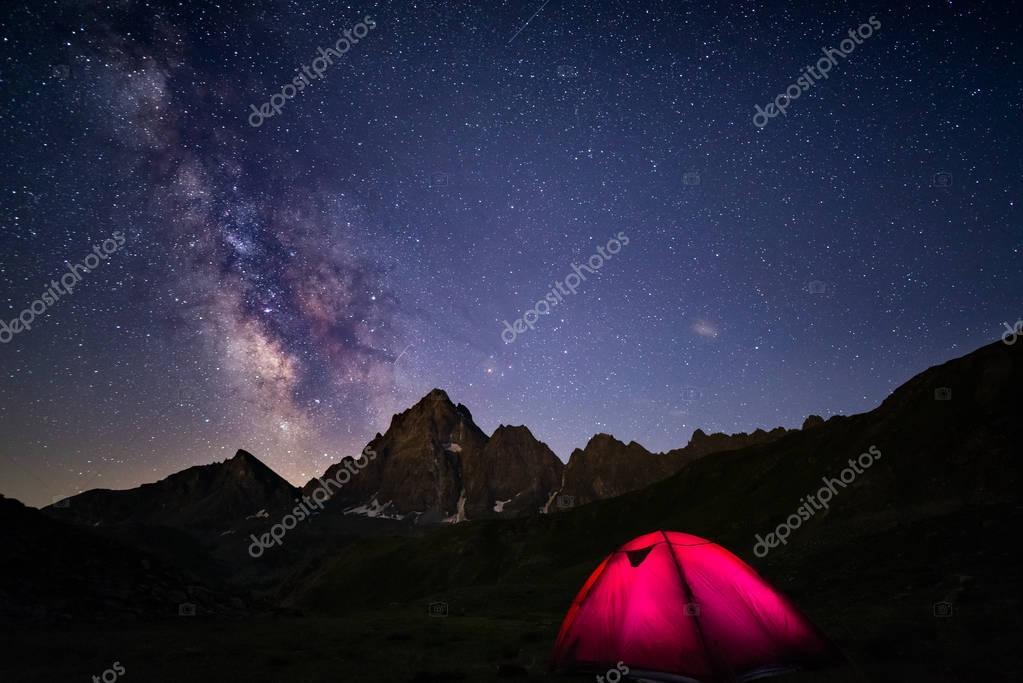 アルプスの標高の高い星空と天の川の下でのキャンプ。背景に前景と雄大な山のピークで照らされたテント。冒険と探検夏. — ストック画像