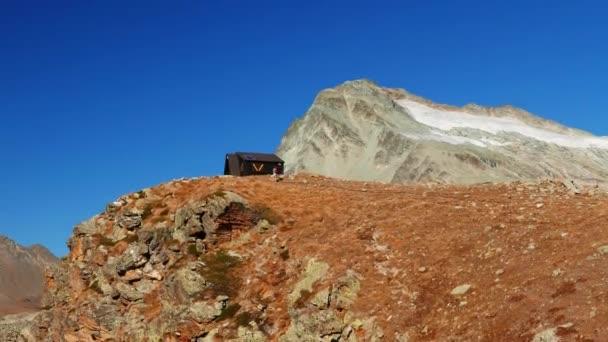Žena dosáhne horské chatě na vrcholu ve vysoké nadmořské výšce skalnaté krajině s ledovci a peak v pozadí. Dobrodružství na Alpy
