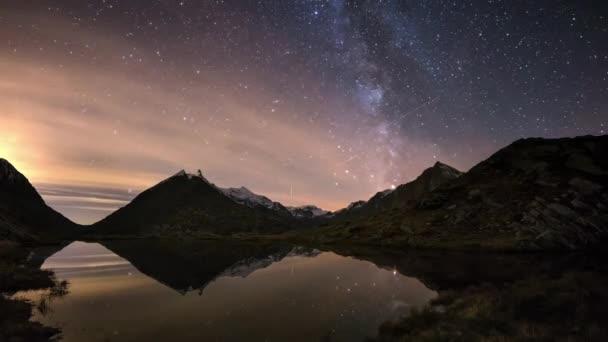 Mléčné dráhy čas zanikla hvězdnou oblohu nad zasněžené horský hřeben, odráží na idylické apine jezero