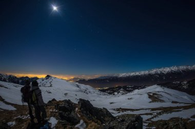 Moon and starry sky, snow on the Alps, fisheye lens. Orion Constellation, Betelgeuse and Sirio. Long exposure blurred two hikers looking at view, night outdoor activities.