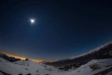Turin city lights, night view from snow covered Alps by moonlight. Moon and Orion constellation, clear sky, fisheye lens. Italy.