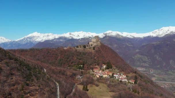 Antenne: Drohnenflug über Wald zeigt schneebedeckte Berge und Sacra di San Michele (Abtei des Heiligen Michels) auf dem Gipfel, Turin, Italien