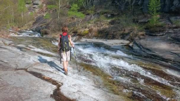 Woman backpacker walking on rock exploring waterfall in alpine valley, freedom backpacking travel concept