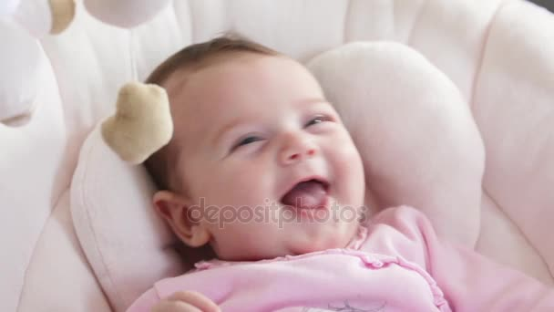 Close up of newborn baby girl smiling in the baby rocker stock video