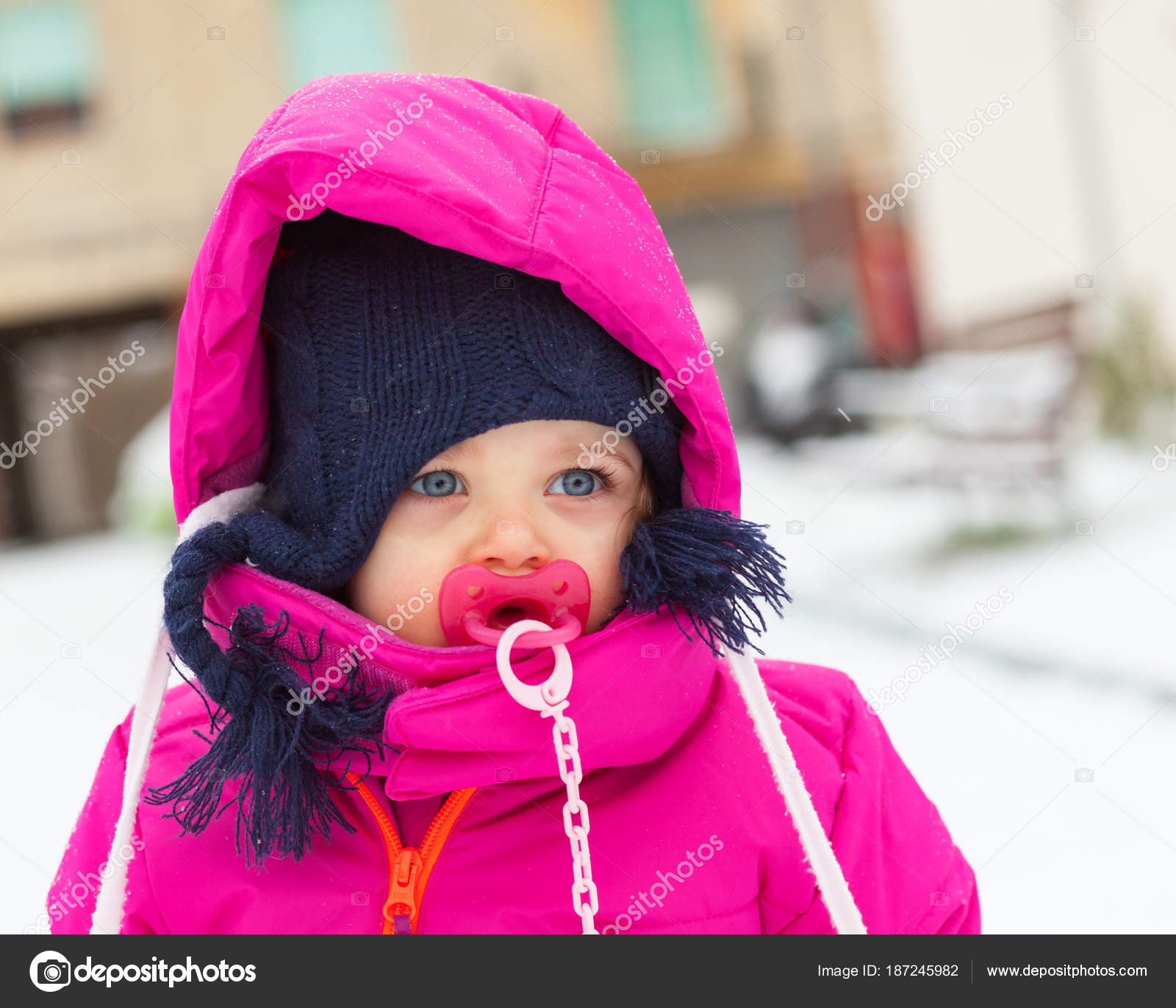 c415f0e4e Toddler baby girl in a magenta snow suit playing on the snow ...