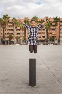 Little girl jumping in the middle of the street