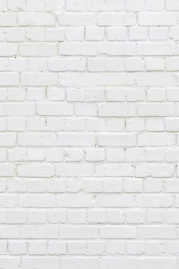 White painted brick wall. White background of bricks. Bricks whitewall. Abstract texture background. Vertical orientation.