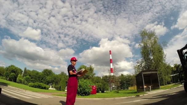 Industriearbeiter mit roter Mütze beim Betrachten eines Dokuments vor einer Fabrik