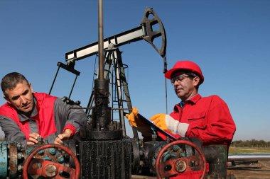Engineers Inspecting Oil Field Equipment