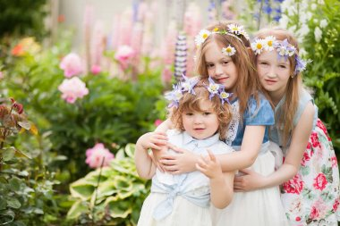 three little sisters embrace in the garden