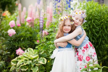 two little sisters embrace in the garden