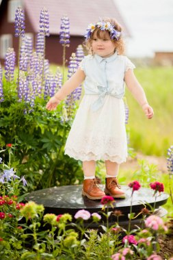 happy toddler girl with a flower wreath in the garden