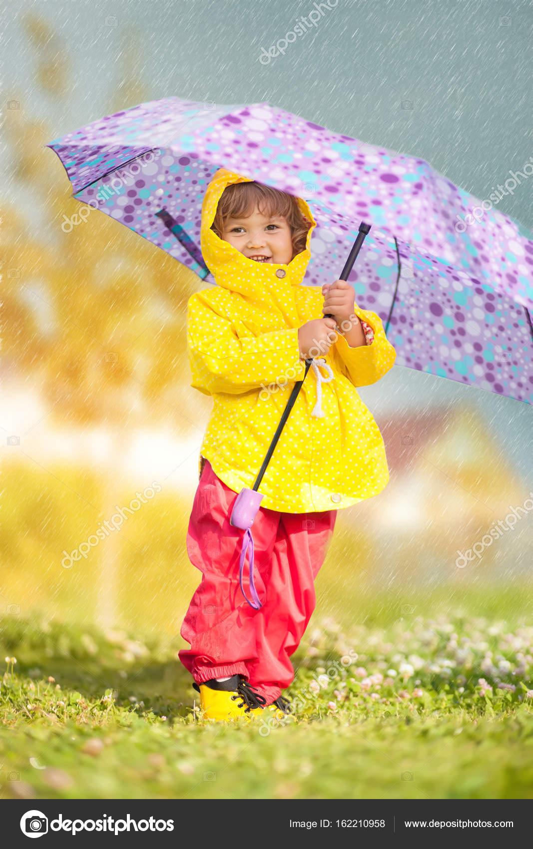 Día De Lluvia Muchacha Del Niño Feliz Con Abrigo Impermeable Con