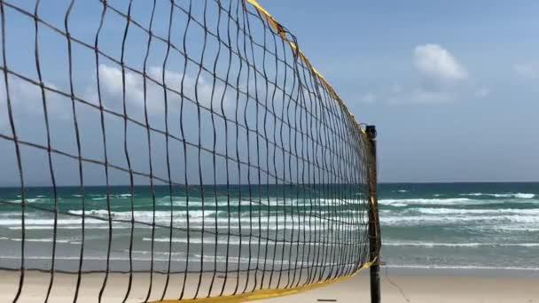 Plážové volejbalové hřiště na písečném břehu u moře.