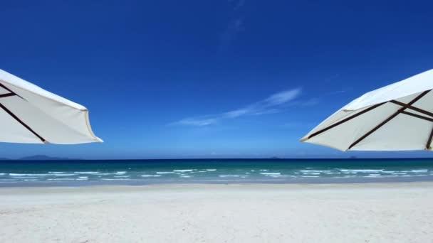Seelandschaft durch zwei große weiße Sonnenschirme, an einem leeren weißen Sandstrand, mit blauem Meer