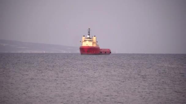 Egy vörös hajó áll a part mellett, a nyílt tengeren, az óceánon, nyáron. Limassol, Ciprus, 4k