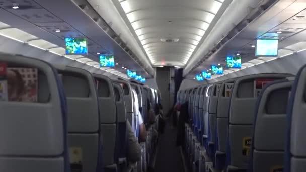 Moskva - Mart,09,2020. Třída Economy Cestující v letadle sedí na svých sedadlech. obsahuje šum a vibrace. Editorial