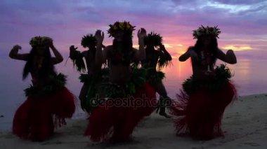 hula dancers performing at sunset
