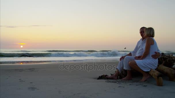 pár na pláži při západu slunce