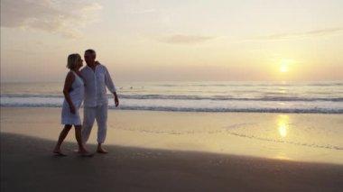 seniors walking on beach