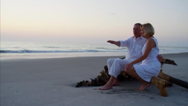 Senioři na pláži při západu slunce