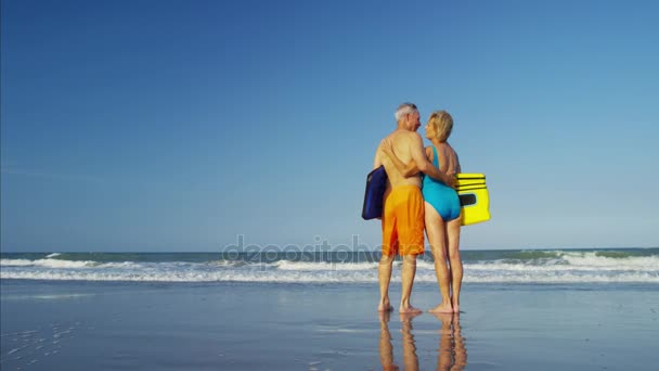 couple with bodyboards on the beach