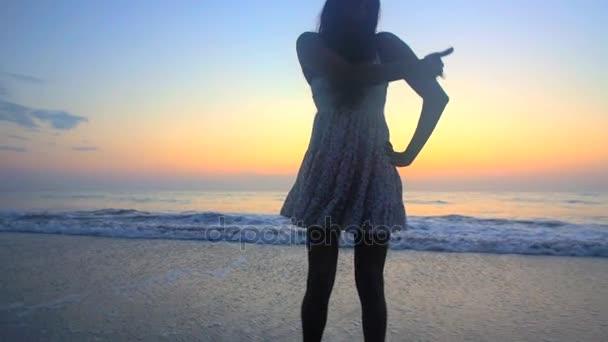 Маленькая девочка на пляже танцует сексуальный танец