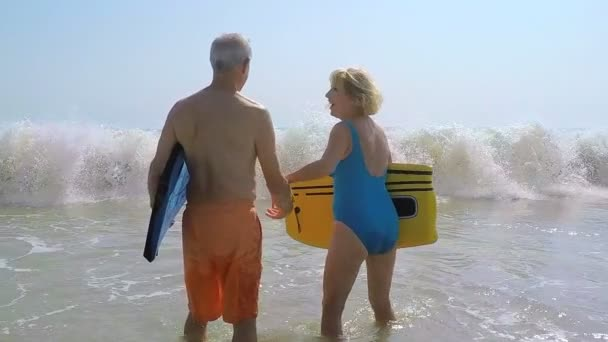 couple holding body boards