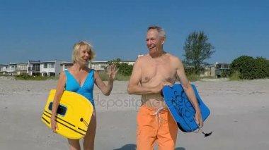couple walking with bodyboards