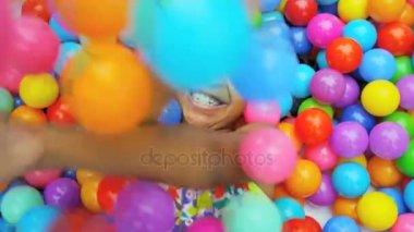 girl playing in pool full balls