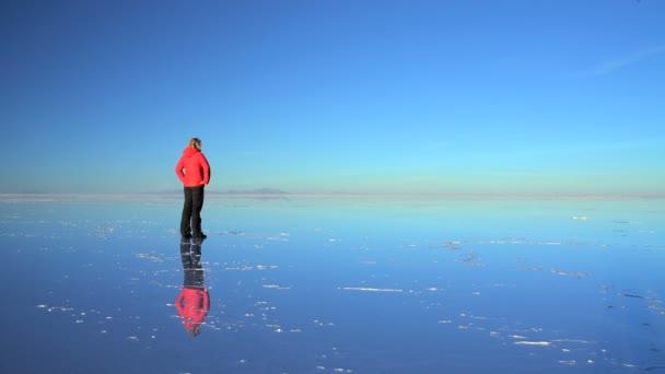 Tourist At Sunset Viewing The Bolivian Salar De Uyuni
