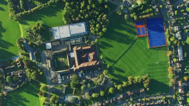 aerial overhead rooftop view at sunrise london suburban community neighborhood sports facilities residential houses and streets england uk stock footage